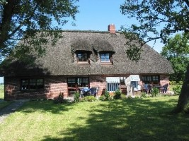 """Gartenansicht auf das Haus mit Terrasse, Liegewiese, Strandkorb Tisch und Stühle, Grillecke. / Ferienwohnung """"Ferienhaus Neukoog  I"""" in Nordstrand"""
