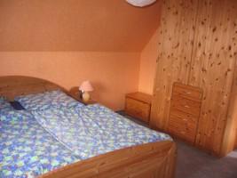 """Gemütliches Schlafzimmer mit zusätzlichem Kinderbett. Ein Fernseher ist vorhanden. / Ferienwohnung """"Ferienwohnung Hansen"""" in Husum"""