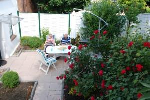 """Der gemütliche Rosengarten mit Gartenmöbeln und Sonneschirm lädt zum Entspannen ein. / Ferienwohnung """"Altstadtidyll -Gartenidyll"""" in Husum / Nordsee"""