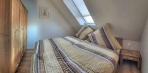 """Ein Schlafzimmer, ausgestattet mit Doppelbett und Schrank / Ferienhaus """"Ferienhaus Niels und Julia"""" in Büsum"""