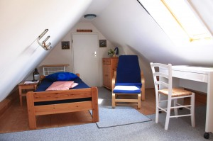 """Schlafzimmer mit Einzelbett, gemütlichem Sessel und Schreibtisch.  / Ferienwohnung """" Möwe"""" in Husum-Schobüll"""
