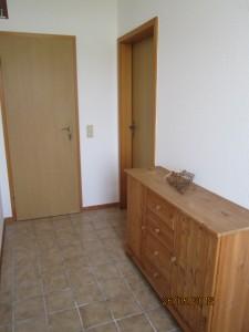"""Der kleine Flur verbindet die einzelnen Räume und hat eine Garderobe und eine kleine Anrichte mit Spielzeug für den Garten / Ferienwohnung """"Haus lütje wehr"""" in Hattstedtermarsch"""