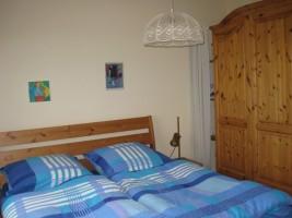 Schlafzimmer mit einem Doppelbett und einem geräumigen Kleiderschrank / Ferienwohnung  in Husum