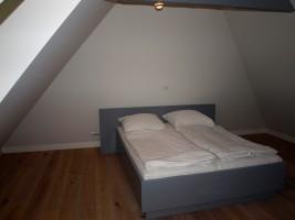 """Schlafzimmer mit Doppelbett und TV im OG / Ferienhaus """"Kate am See"""" in Porrendeich/Uelvesbüll"""