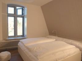 """Schlafzimmer im OG mit TV / Ferienhaus """"Stadthuus 51"""" in Husum"""
