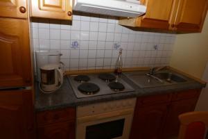 """Küchenzeile mit Backofen, Kühlschrank und Gefrierfach. Eine Waschmaschine befindet sich im Versorgungsraum / Ferienhaus """"Peters"""" in Simonsberg"""