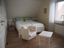 """Großes Schlafzimmer mit Doppelbett 1.60x2.00 m. und TV.  Ansicht 1 / Ferienhaus """"Lat di tied"""" in Husum"""
