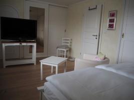 """Großes Schlafzimmer mit Doppelbett 1.60x2.00 m. und TV.  Ansicht 2 / Ferienhaus """"Lat di tied"""" in Husum"""