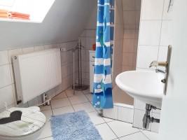 """Das Badezimmer hat eine Dusche, ein Waschbecken und WC, einen Spiegelschrank und einen kleinen Badezimmerschrank / Ferienwohnung """"Erika Kohrt"""" in Husum  OT Schobüll"""