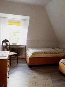 """Das zweite Schlafzimmer hat ein Einzelbett, einen Nachtschrank, eine Kommode und einen Kleiderschrank und einen Stuhl. / Ferienwohnung """"Erika Kohrt"""" in Husum  OT Schobüll"""