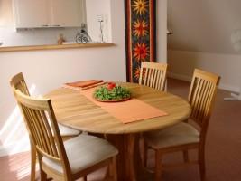 """Essbereich mit 4 Stühlen, dahinter die Durchreiche zur Küche. / Ferienwohnung """"Urlaub am Wattenmeer mit Strandkorb"""" in Finkhaushallig"""