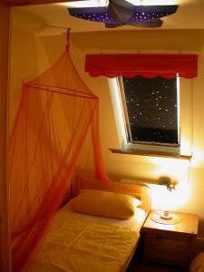 """(Kinder-)Schlafzimmer, abends super kuschelig. / Ferienwohnung """"Urlaub am Wattenmeer mit Strandkorb"""" in Finkhaushallig"""