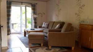 """Wohnzimmer mit einer neuen Sitzgarnitur. / Ferienhaus """"unter der Buche"""" in Husum"""