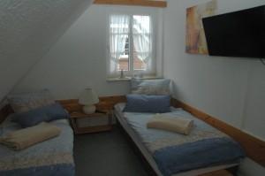 """Schlafzimmer mit Einzelbetten und Fernseher / Ferienhaus """"Muschelsucher 2"""" in Nordstrand-Norderhafen"""