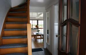 """Eingangsbereich mit Treppe nach oben. Im Hintergrund das Wohnzimmer / Ferienhaus """"Ferienhaus Neukoog II"""" in Nordstrand"""