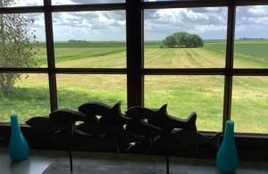 """Schlafzimmer im OG mit einer Sitzecke und einem Fernseher. Das Zimmer hat einen herrlichen Blick über die Landschaft. / Ferienhaus """"Ferienhaus Neukoog II"""" in Nordstrand"""