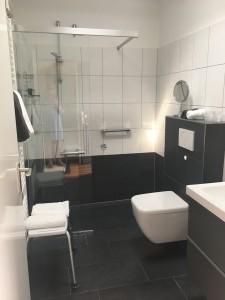 """Bad mit einer begehbaren Dusche, einem modernen WC und einem großen beleuchteten Spiegel. / Ferienhaus """"Bungalow Kleine Auszeit"""" in Husum"""