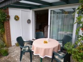 """gemütliche überdachte Terrasse zum Wohlfühlen. frühstücken und grillen -Südseite- mit Blumen  / Ferienhaus """"Haus Seestern"""" in Nordstrand"""