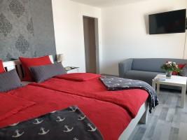 """Das große Schlafzimmer mit zusätzlichem Sofa und Flachbildfernseher / Ferienwohnung """"Kleiner Onkel"""" in Hattstedtermarsch"""
