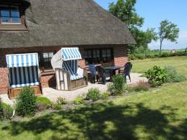 """Ihre Terrasse mit einem Strandkorb und einer Sitzgarnitur für den garten / Ferienwohnung """"Ferienhaus Neukoog  I"""" in Nordstrand"""
